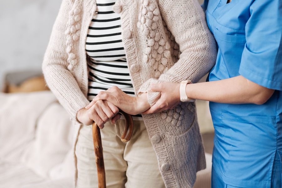 Long Term Care Insurance - Nurse Helping a Woman Walk