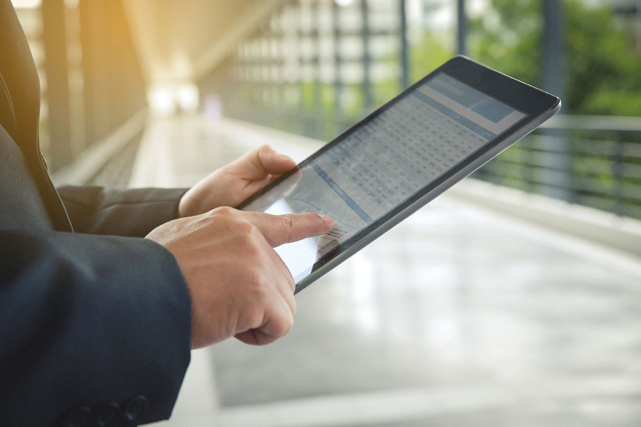 Blog - Businessman Standing in Office Using a Tablet