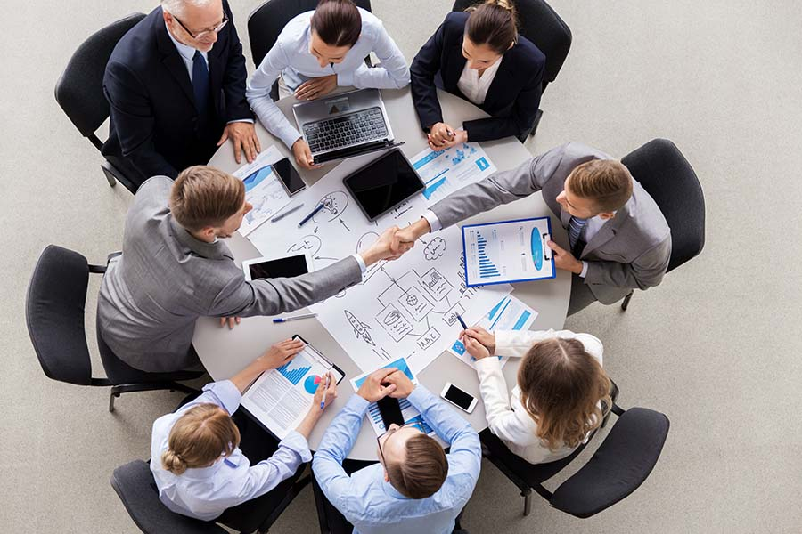Business Insurance - Group of Employees Sitting Around Table in Office During Business Meeting