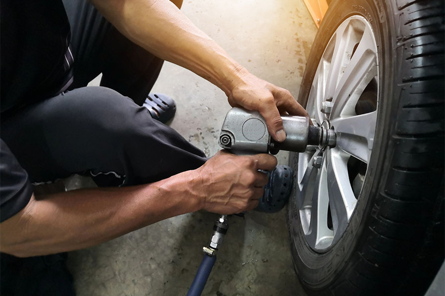 Specialized Business Insurance - Mechanic Changing Tires at a Repair Shop Garage